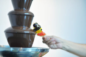 liquid chocolate fountain and fresh fruits on stick